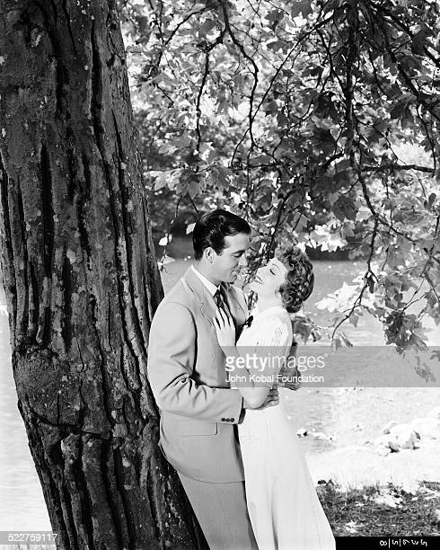 Portrait of actress Claudette Colbert and an actor leaning against a tree in a romantic embrace for Paramount Pictures circa 1935