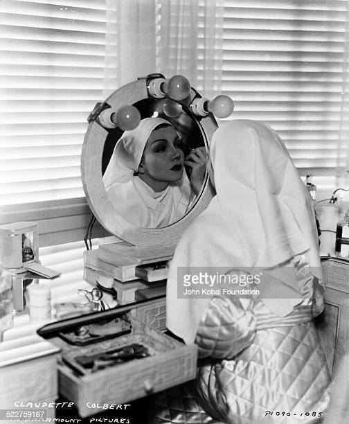 Portrait of actress Claudette Colbert applying makeup at a dressing table mirror for Paramount Pictures 1935