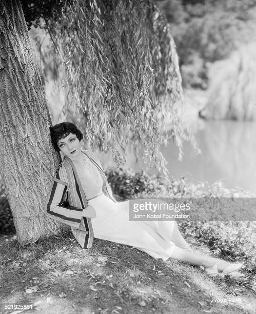 Portrait of actress Claudette Colbert leaning against a tree next to a lake for Paramount Pictures 1930