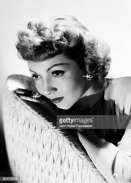 Portrait of actress Claudette Colbert leaning on the back of a chair for Selznick International Pictures 1944