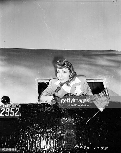 Portrait of actress Claudette Colbert leaning out of the window of a train for Paramount Pictures 1943