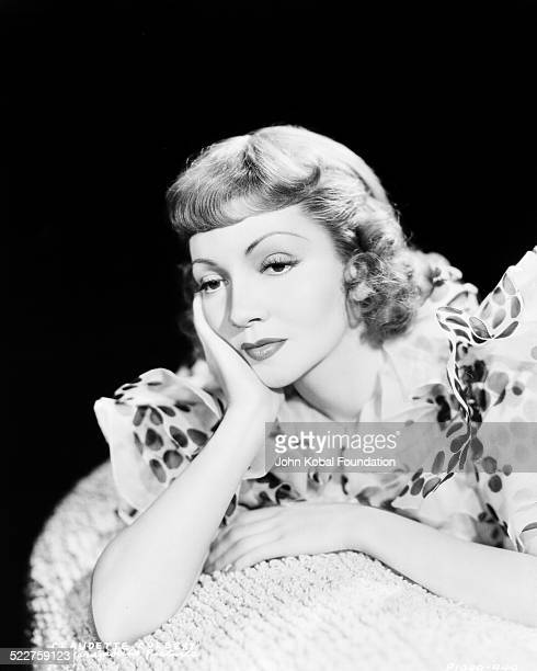 Portrait of actress Claudette Colbert posing with her head resting on her hand for Paramount Pictures 1938