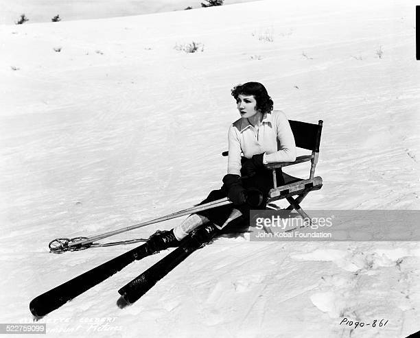 Portrait of actress Claudette Colbert resting in a chair on a snow slope whilst wearing skis for Paramount Pictures 1932