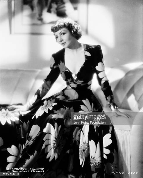 Portrait of actress Claudette Colbert sitting down wearing a long floral dress for Paramount Pictures 1938