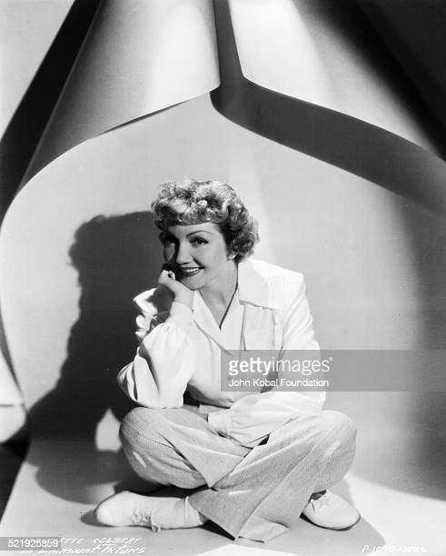 Portrait of actress Claudette Colbert sitting down with her legs crossed for Paramount Pictures 1937