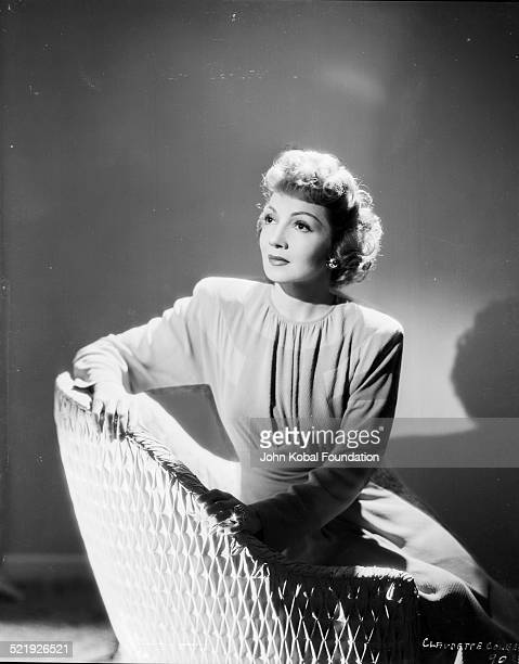 Portrait of actress Claudette Colbert sitting in a wicker chair for Selznick Productions 1944