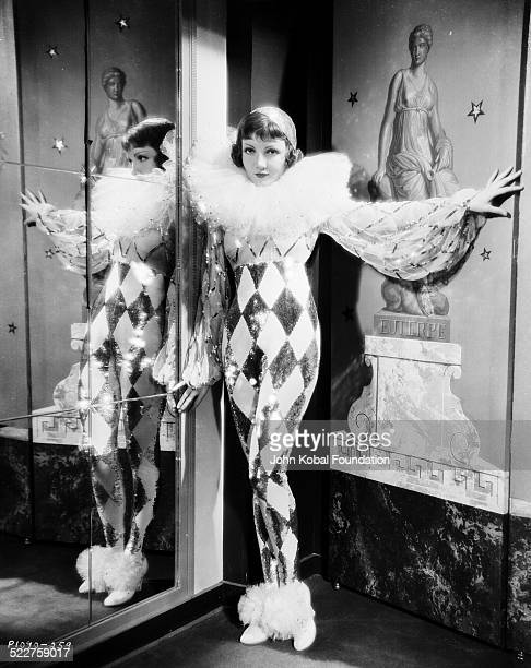 Portrait of actress Claudette Colbert standing in front of a mirror wearing a ruff around her neck and a sequined costume as she appears in the movie...