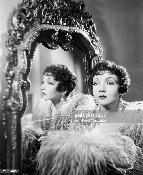 Portrait of actress Claudette Colbert standing next to an ornate mirror for Paramount Pictures 1932