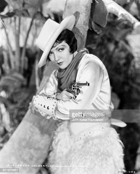 Portrait of actress Claudette Colbert wearing a cowboy costume and holding a gun for Paramount Pictures 1930