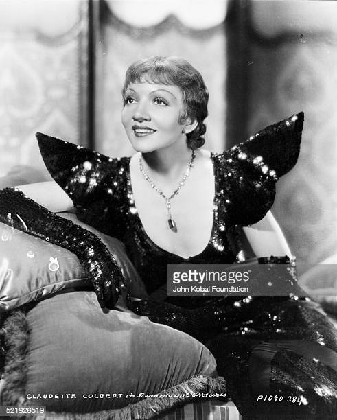 Portrait of actress Claudette Colbert wearing a glittery gown for Paramount Pictures 1933