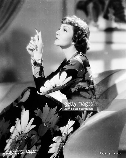 Portrait of actress Claudette Colbert wearing a long floral dress and smoking a cigarette for Paramount Pictures 1938