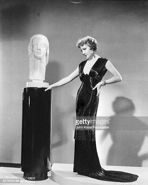 Portrait of actress Claudette Colbert wearing a low cut dress and standing next to a statue for Paramount Pictures 1932