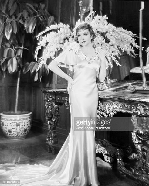 Portrait of actress Claudette Colbert wearing a silk evening gown for Paramount Pictures 1934