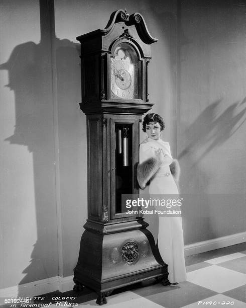Portrait of actress Claudette Colbert wearing an evening dress and leaning against a grandfather clock for Paramount Pictures 1929