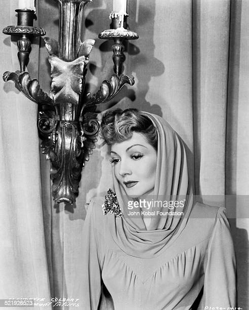 Portrait of actress Claudette Colbert wearing an evening gown and head scarf for Paramount Pictures 1934