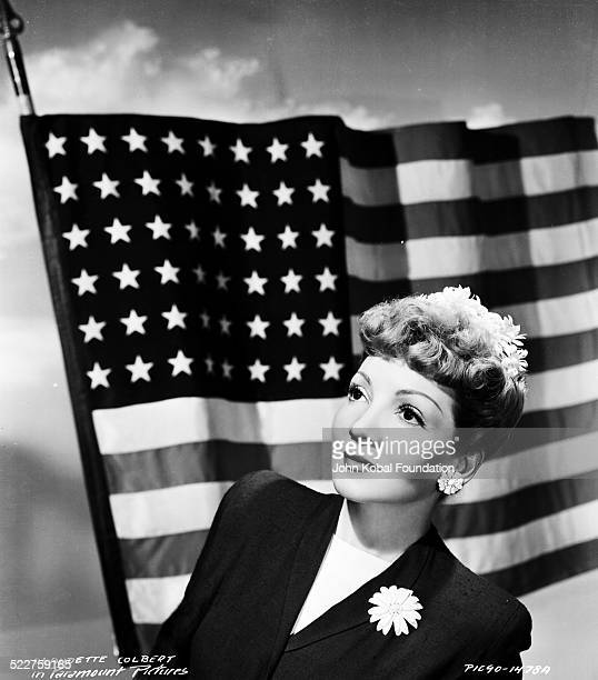Portrait of actress Claudette Colbert wearing flower earrings and brooch in front of the American flag for Paramount Pictures 1941