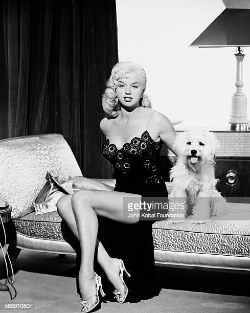 Portrait of actress Diana Dors sitting on a chaise longue with her pet dog 1951