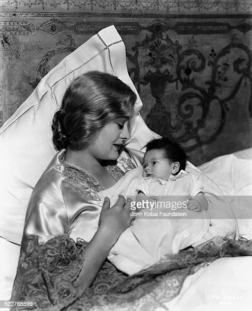 Portrait of actress Dolores Costello Barrymore in bed holding her newborn baby for MGM Studios June 23rd 1932