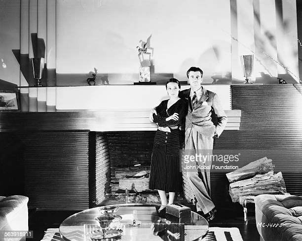 Portrait of actress Dolores del Rio and her husband art director Cedric Gibbons standing next to a fireplace for MGM Studios 1931