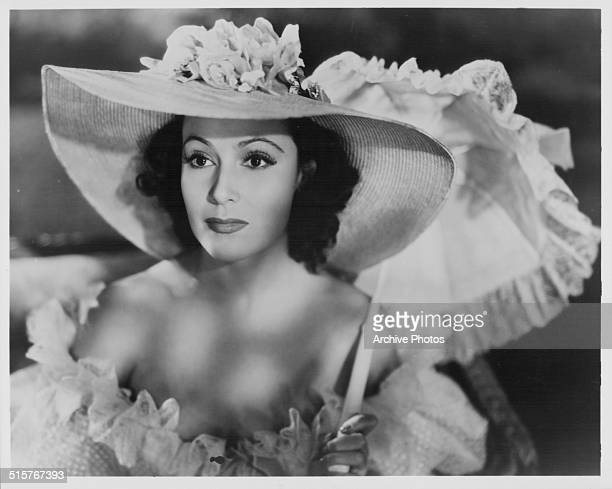 Portrait of actress Dolores del Rio wearing a large hat and holding a parasol in a film still circa 1920