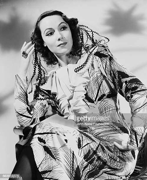 Portrait of actress Dolores del Rio wearing a patterned dress with a ruffled neckline for Warner Bros Pictures 1935