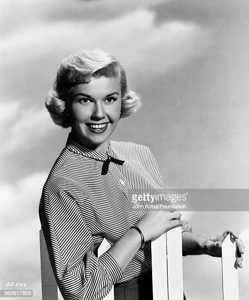 Portrait of actress Doris Day leaning on a picket fence and wearing a buttonedup blouse for Warner Bros Studios 1951