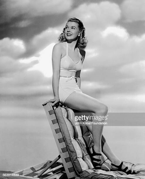 Portrait of actress Doris Day sitting on a sun lounger wearing a bathing suit for Warner Bros Studios 1951