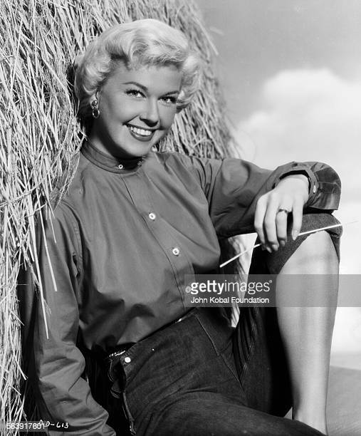 Portrait of actress Doris Day wearing jeans and leaning against a bale of hay for Warner Bros Studios 1951