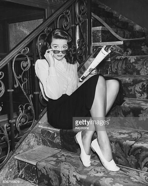 Portrait of actress Dorothy Malone sitting on a staircase reading a magazine and wearing sunglasses circa 1940