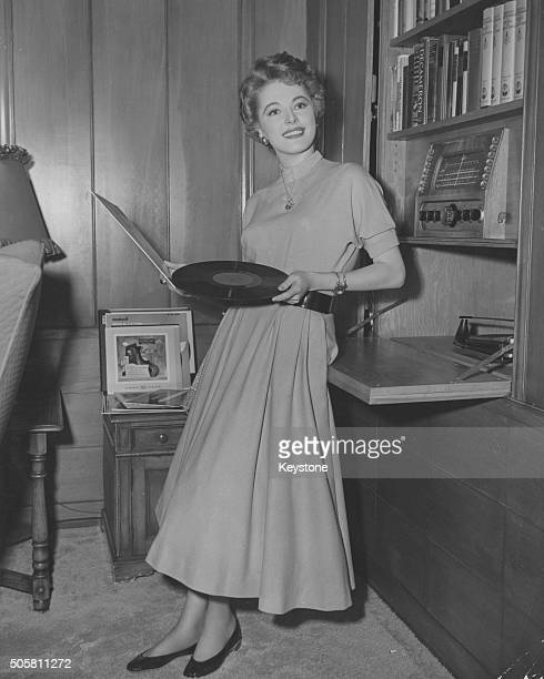Portrait of actress Eleanor Parker playing records in her home Los Angeles circa 1955