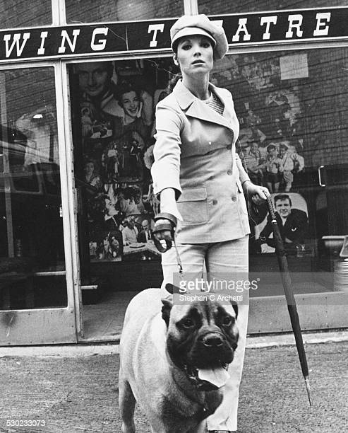 Portrait of actress Elsa Martinelli holding a dog on a leash and wearing a trouser suit and cap while filming 'Maroc 7' at Pinewood Studios London...