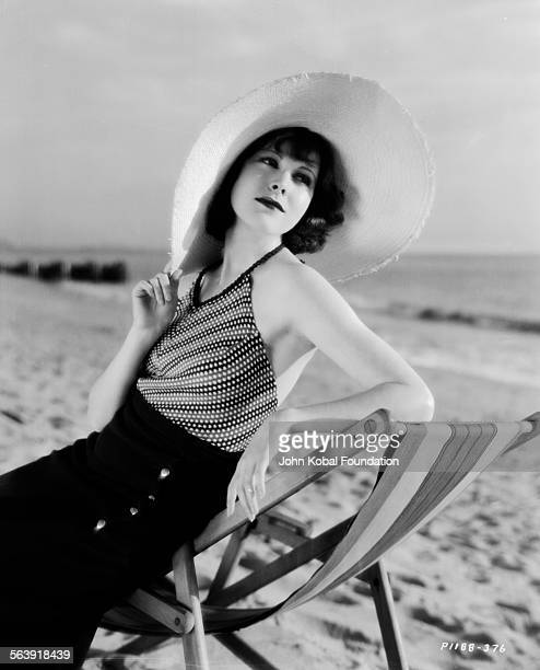 Portrait of actress Frances Dee sitting on a deck chair wearing a large sun hat for Paramount Pictures 1932