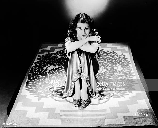 Portrait of actress Frances Dee sitting on the floor with her knees to her chin for Paramount Pictures 1930