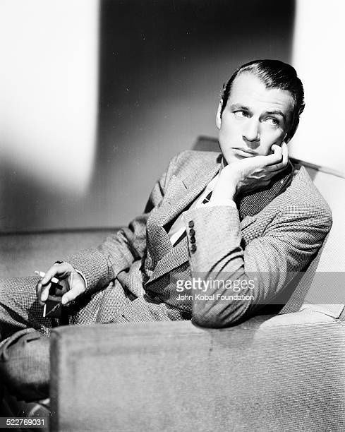 Portrait of actress Gary Cooper wearing a suit and smoking a cigarette, for MGM Studios, April 17th 1934.