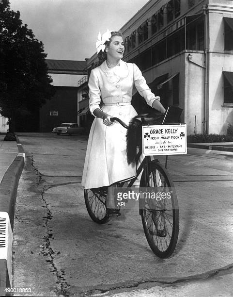 Portrait of actress Grace Kelly on a bicycle in 1954.