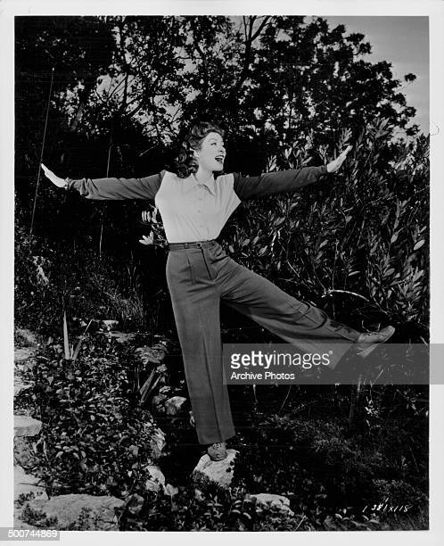 Portrait of actress Greer Garson dancing on rocks outdoors 1949