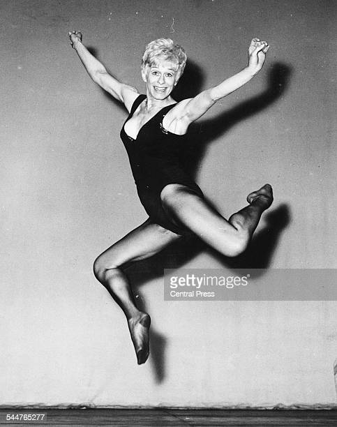 Portrait of actress Gretchen Wyler wearing tights and a leotard and jumping in the air limbering up for her role in the musical 'Sweet Charity' at...