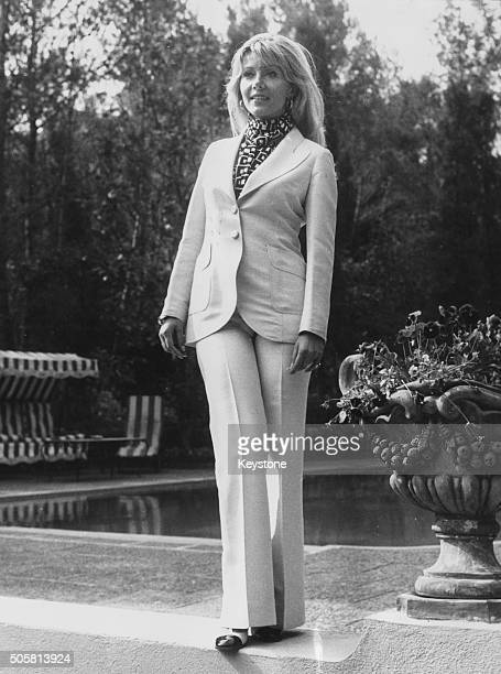 Portrait of actress Ingrid Pitt wearing a white trouser suit and standing next to a pool at a press reception for the opening of the 10th...