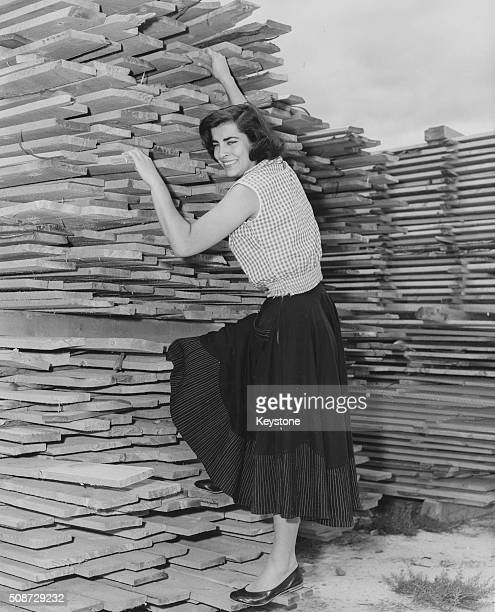 Portrait of actress Irene Papas wearing a skirt and flat shoes as she tries to climb a pile of wood circa 1960