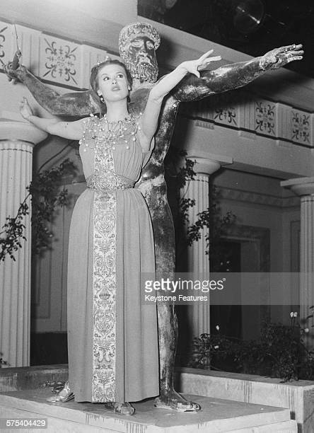 Portrait of actress Irene Tunc wearing an Ancient Greek costume as she performs a dance with a Pagan statue, filming a scene for 'Aphrodite, Goddess...
