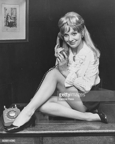 Portrait of actress Jacki Piper sitting on a desk holding a telephone promoting the role in the play 'The Secretary Bird' at the Savoy Theatre London...