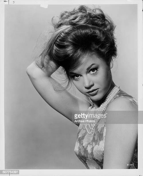 Portrait of actress Jane Fonda holding her hair oiled on top of her head circa 1965