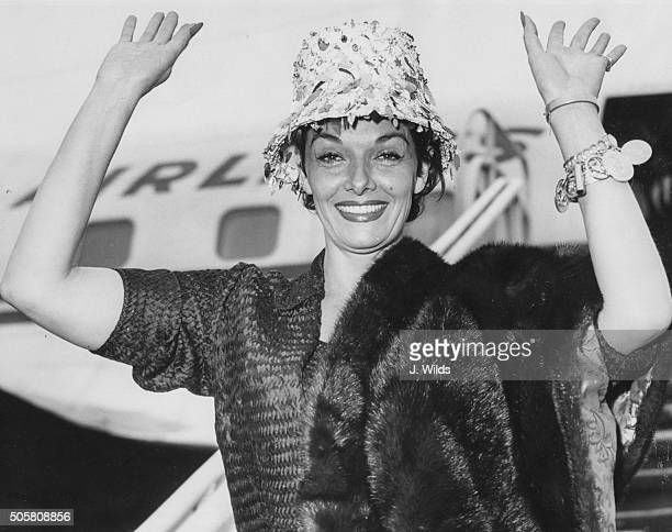 Portrait of actress Jane Russell waving as she arrives in the country to appear on the television show 'Sunday Night at the London Palladium' at...