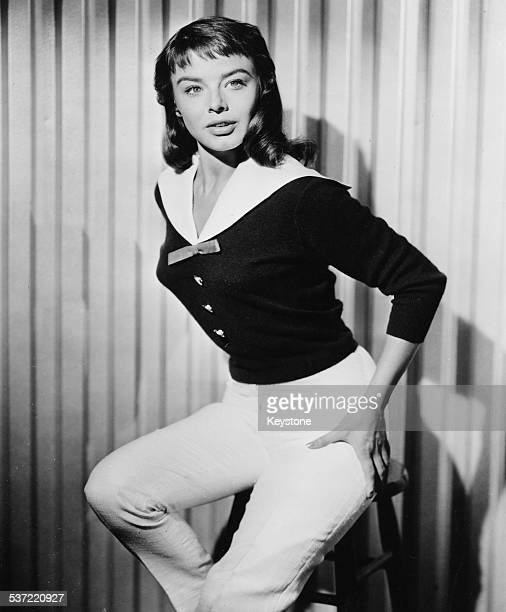 Portrait of actress Janet Munro perched on a stool circa 1955