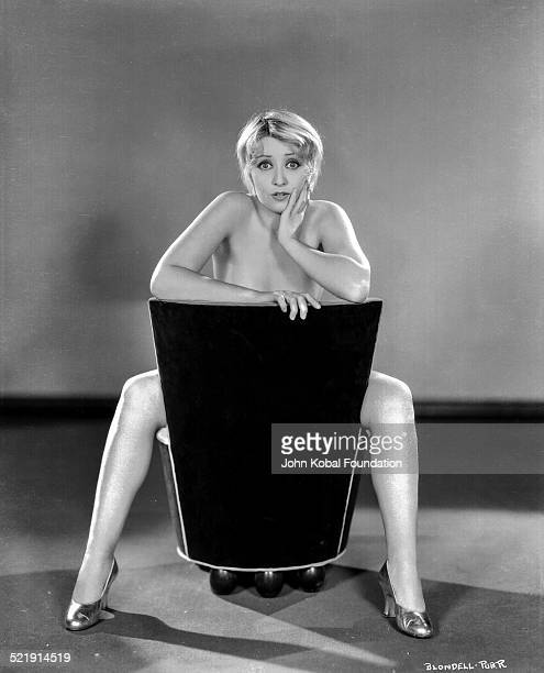 Portrait of actress Joan Blondell posing nude behind a chair for Warner Bros Studios 1933