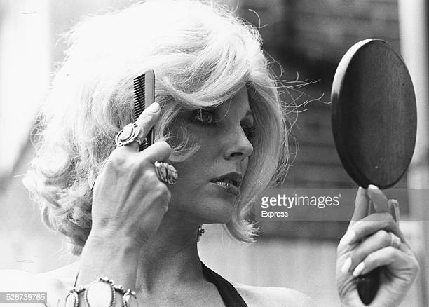 Portrait of actress Joan Collins brushing a blonde wig on her head, preparing to play the role of Marilyn Monroe in the play 'Legend', London, July...