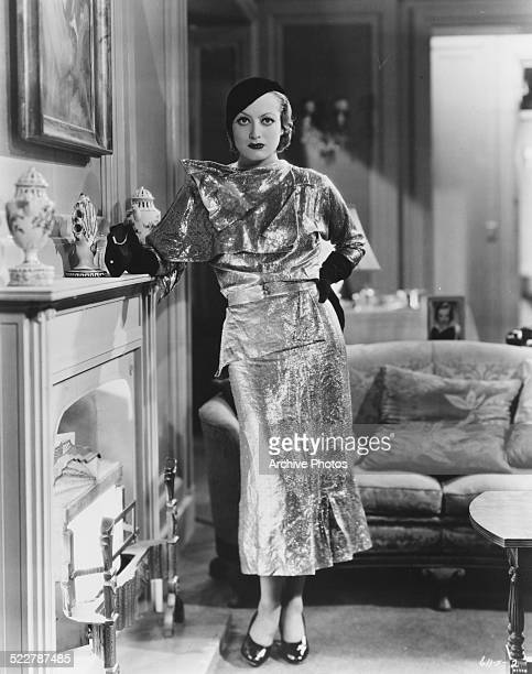 Portrait of actress Joan Crawford wearing a matching sequin outfit with back gloves and beret standing by a fireplace circa 1930