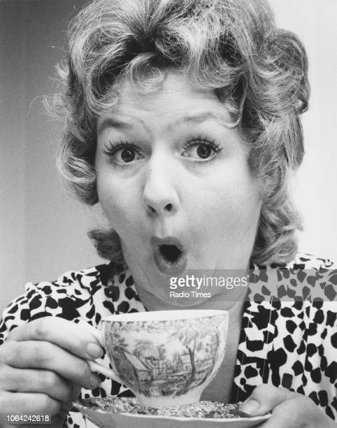 Portrait of actress Joan Sims mugging for the camera as she drinks a cup of tea August 1971