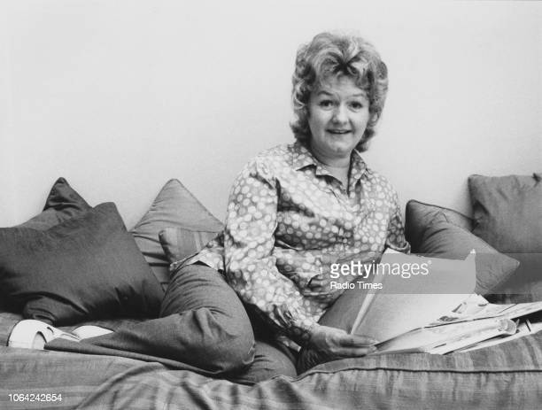 Portrait of actress Joan Sims reclining on a sofa and reading a newspaper August 1971