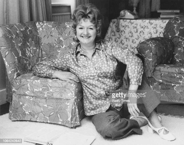 Portrait of actress Joan Sims sitting on the floor reading a newspaper August 1971